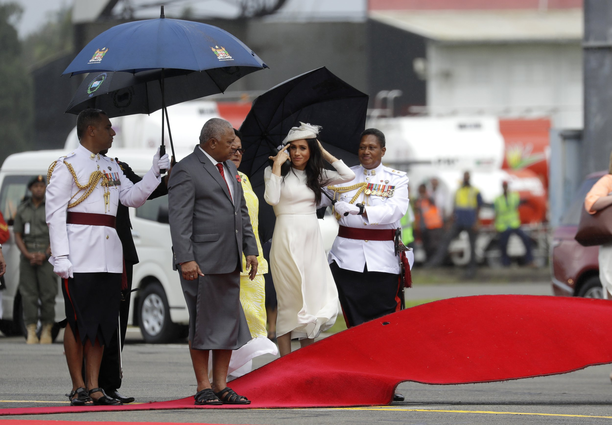 Meghan, Duchess of Sussex waits with Fiji Prime Minister Frank Bainimarama, left, as a red carpet is laid during a welcome ceremony in Suva, Fiji, Tuesday, Oct. 23, 2018. Britain's Prince Harry and his wife Meghan are on day eight of their 16-day tour of Australia and the South Pacific.(AP Photo/Kirsty Wigglesworth,Pool)