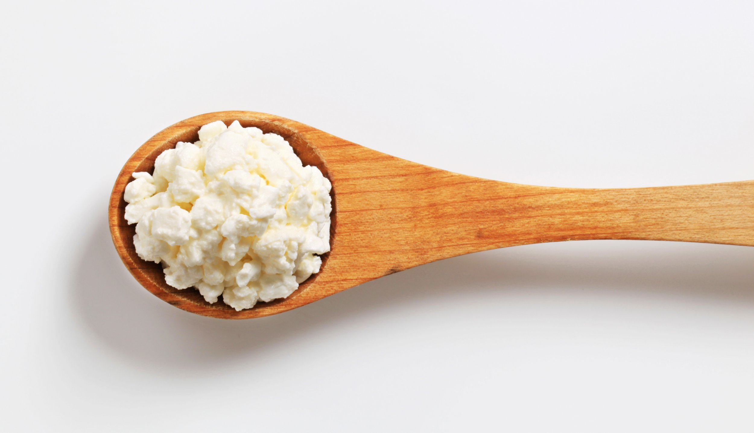 fresh cottage cheese on a deep wooden spoon