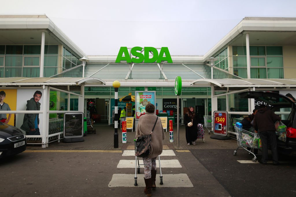 FILE: A customer pushes a shopping cart as she walks towards an Asda supermarket, operated by Wal-Mart Stores Inc., in the Wembley district of London, U.K., on Friday, Nov. 28, 2014. U.K. grocer J Sainsbury Plc plans to buy Walmart Inc.s Asda in a 7.3 billion-pound ($10 billion) deal that would transform the countrys supermarket industry and leave the U.S. retailer as the combined companys biggest shareholder. Our editors select the best archive images of the two supermarket chains. Photographer: Simon Dawson/Bloomberg via Getty Images