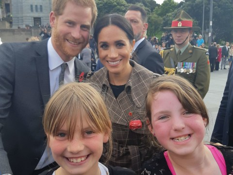 Girls get photo of a lifetime with smiling Harry and Meghan in the background