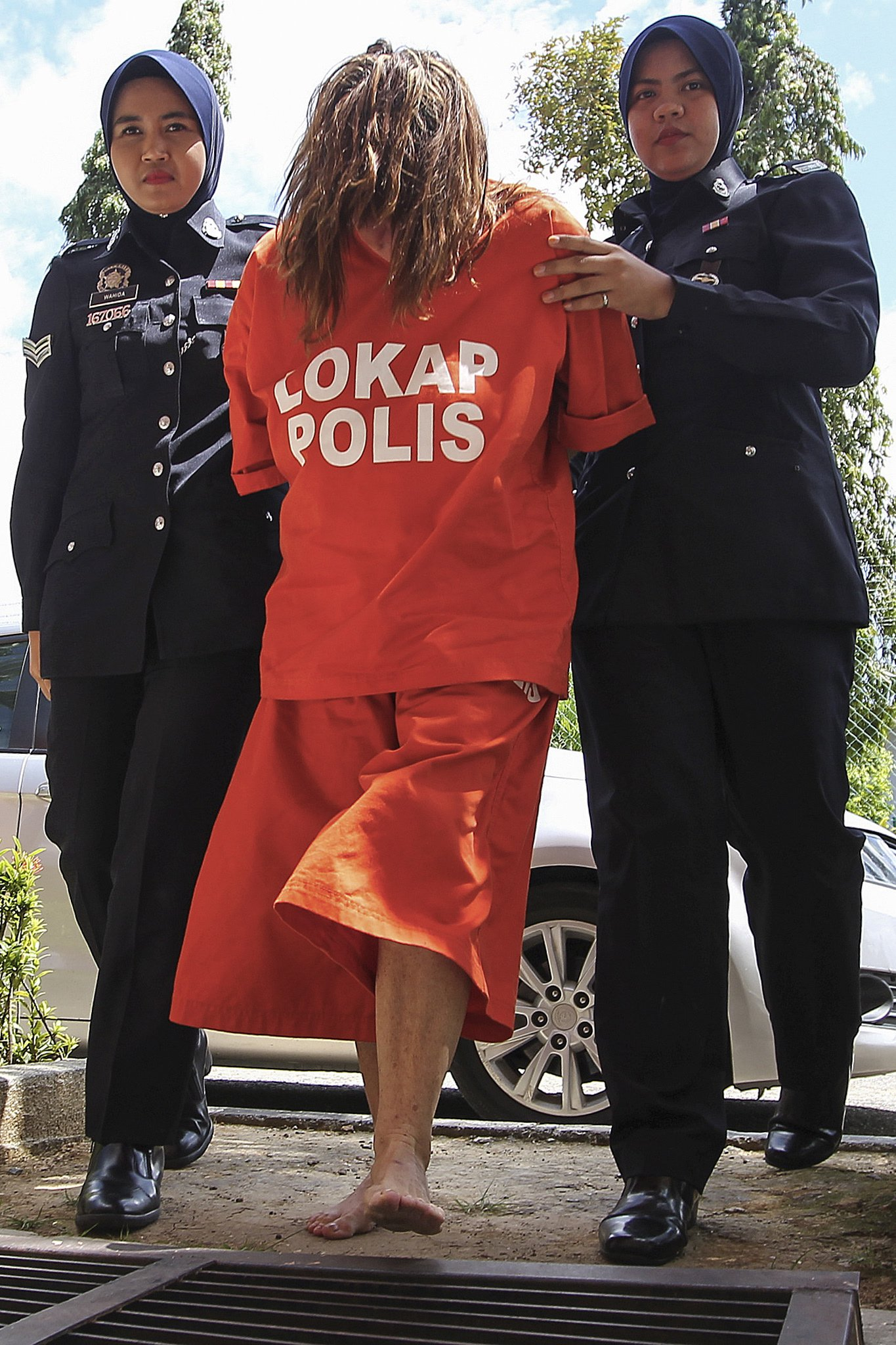 epa07130440 Samantha Williams (C), 61, is escorted by a Royal Malaysian Police officer as they arrive at Langkawi court, state of Kedah, Malaysia, 30 October 2018. Samantha Williams has been arrested on 18 October for the alleged murder of her husband John William Jones, 62, who was found on the floor of their house with a stab wound to the chest with a kitchen knife in Malaysia. EPA/STR