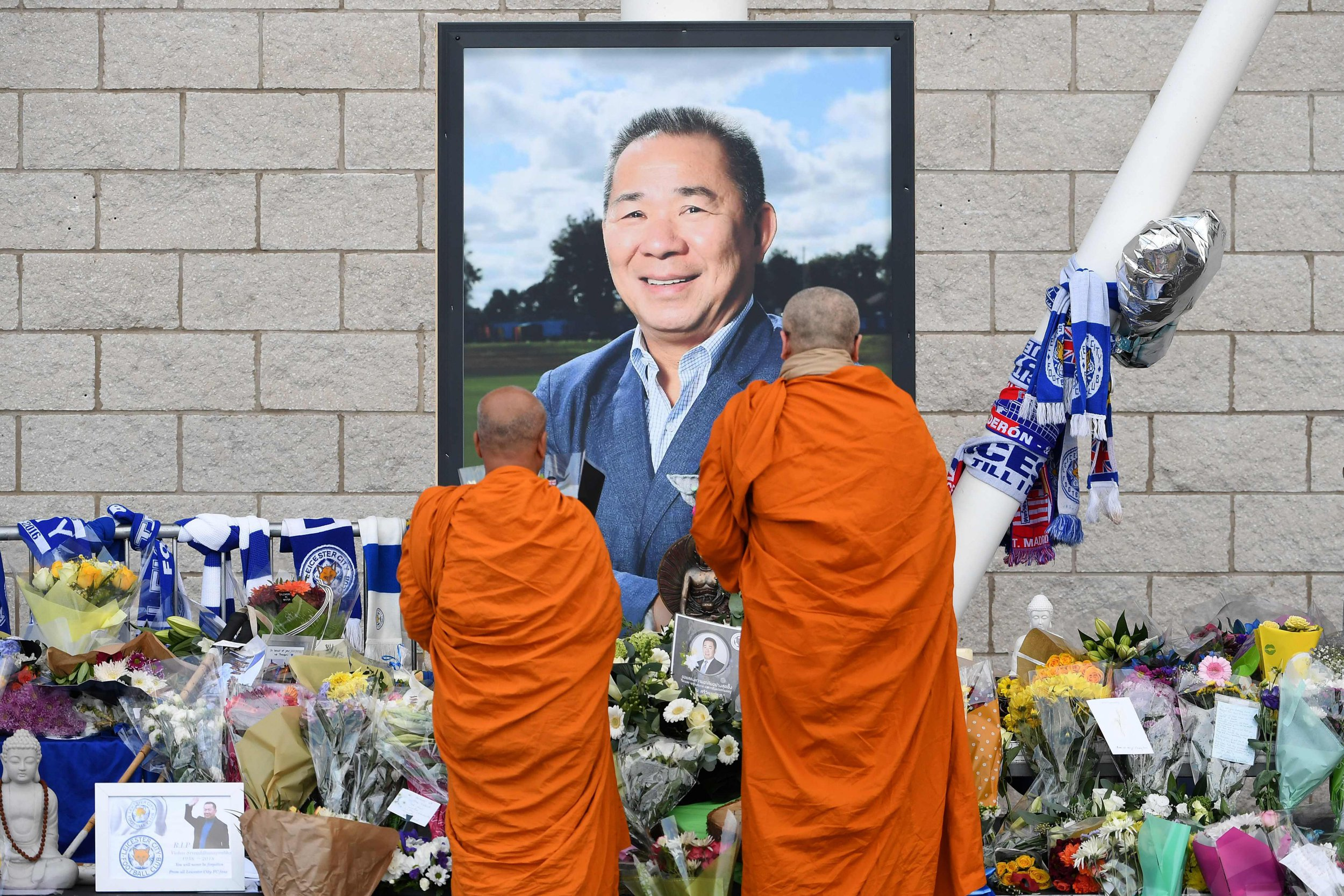 Buddhist monks lay tributes by a photograph of Leicester City Football Club's Thai chairman Vichai Srivaddhanaprabha, outside Leicester City Football Club's King Power Stadium in Leicester, eastern England, on October 31, 2018 in honour and remembrance of those who died in a helicopter crash at the club's stadium on October 27 including the club's Thai chairman Vichai Srivaddhanaprabha. - Leicester City's chairman Vichai Srivaddhanaprabha was among five people killed when his helicopter crashed and burst into flames in the Premier League side's stadium car park moments after taking off from the pitch, the club said on October 28. A stream of fans already fearing the worst had laid out flowers, football scarves and Buddhist prayers outside the club's King Power stadium after Saturday's accident in tribute to the Thai billionaire boss -- the man they credit for an against-all-odds Premier League victory in 2016 (Photo by Paul ELLIS / AFP)PAUL ELLIS/AFP/Getty Images