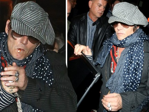 Johnny Depp coolly puffs on a cigarette after watching Rolling Stones rockers perform in London