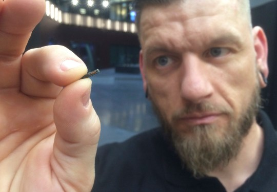 Self-described ???body hacker??? Jowan Osterlund from Biohax Sweden, holds a small microchip implant, similar to those implanted into workers at the Epicenter digital innovation business centre during a party at the co-working space in central Stockholm, Tuesday March 14, 2017. Microchips are being implanted into volunteers to help them open doors and operate office equipment, and its become so popular that members of the Epicentre cyborg club hold regular parties for those with the tiny chips embedded in their hands. (AP Photo/James Brooks)