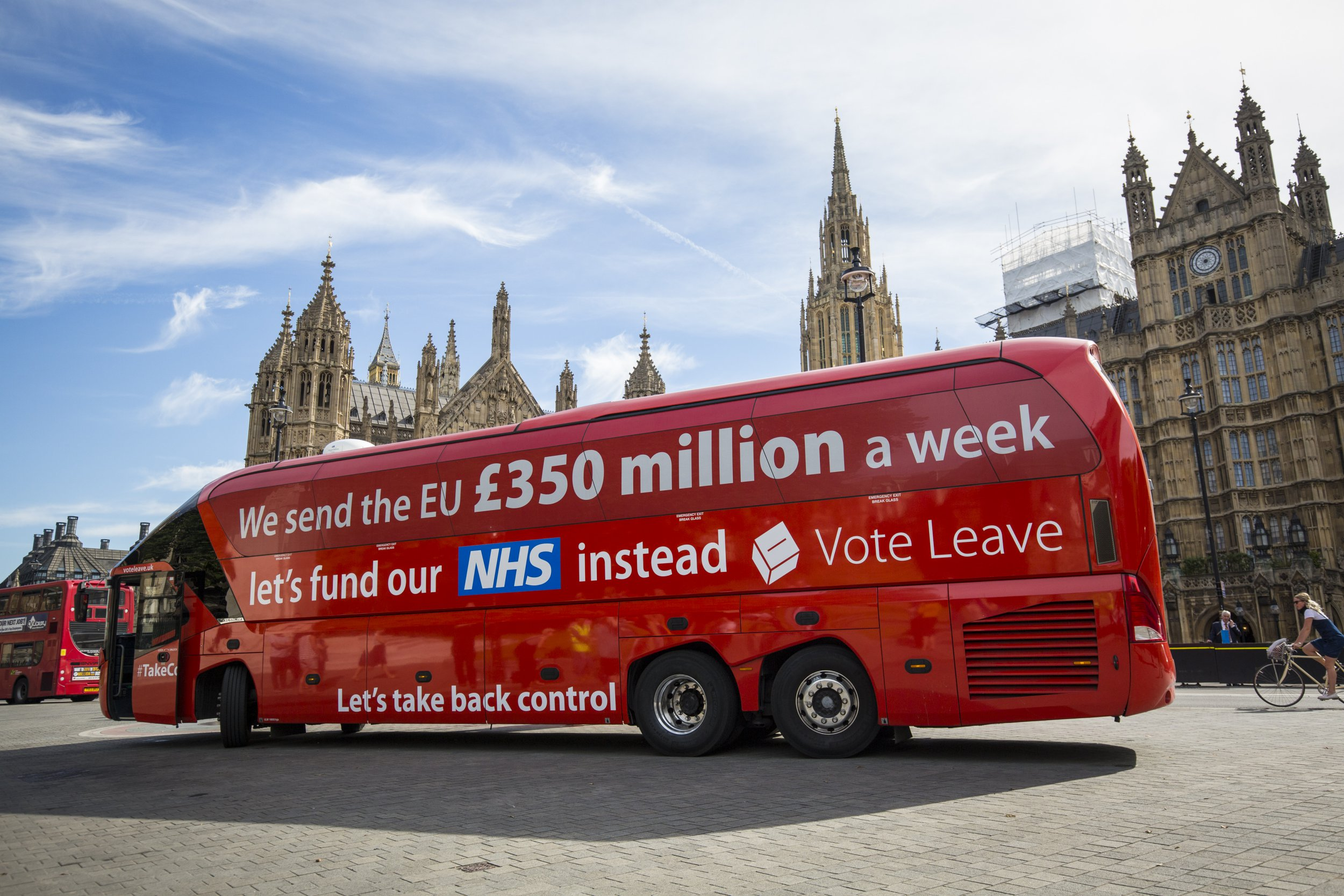 """LONDON, ENGLAND - JULY 18: A 'Vote LEAVE' battle bus is parked outside the Houses of Parliament in Westminster by the environmental campaign group Greenpeace before being re-branded on July 18, 2016 in London, England. The bus which was used during the European Union (EU) referendum campaign and had the statement """"We send the EU ??350 million a week let's fund our NHS instead"""" along the side was today covered with thousands of questions for the new Prime Minister Theresa May and her government about what a 'Brexit' might mean for the environment. (Photo by Jack Taylor/Getty Images)"""