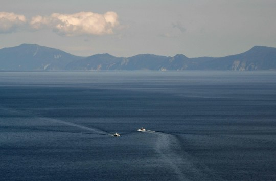 This picture taken on October 10, 2018 shows Kunashiri island, part of an archipelago under Russian control, visible from the Rausu Kunashiri Observatory Deck in Rausu, Hokkaido prefecture. - Four of the islands known as the Northern Territories in Japan and the southern Kuril islands in Russia are disputed and remain a bitter sticking point between Tokyo and Moscow, preventing them from signing a formal peace treaty. Now, former residents who were children when the Soviet troops arrived are heading into their twilight years with little expectation of returning to their former home. (Photo by Kazuhiro NOGI / AFP) / TO GO WITH AFP STORY JAPAN-RUSSIA-DIPLOMACY-POLITICS-WWII,FEATURE BY MIWA SUZUKIKAZUHIRO NOGI/AFP/Getty Images