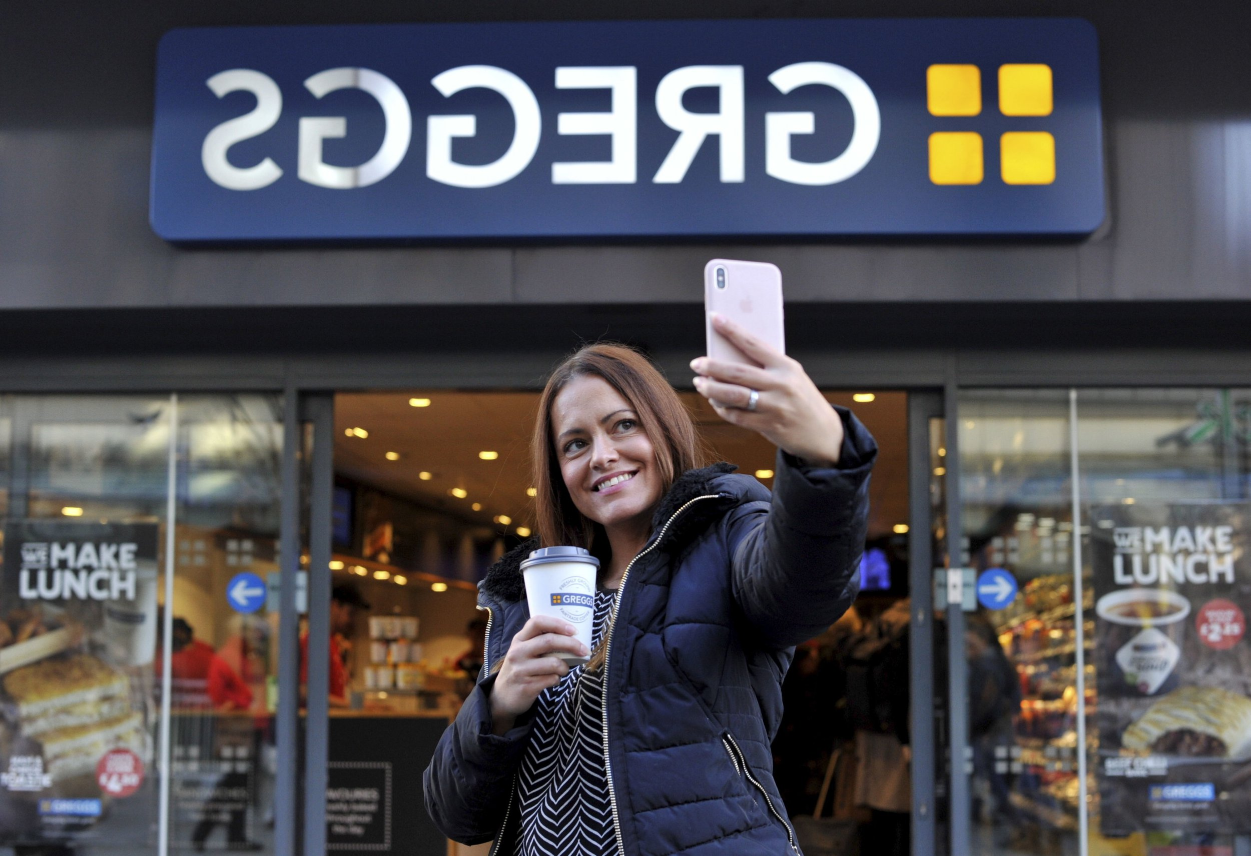 Handout photo issued by Greggs of customer Jennifer Cornell taking a selfie with the new backwards sign at Greggs bakery on Northumberland Street in Newcastle upon Tyne, which is a mirror image so the sign reads the correct way when reflected on the famous Fenwick Christmas window opposite. PRESS ASSOCIATION Photo. Issue date: Friday November 2, 2018. The Fenwick window is being unveiled on Friday evening and each year many thousands of North East families queue up to see the displays which are a seen by many shoppers as an essential part of Christmas. See PA story CONSUMER Greggs. Photo credit should read: Greggs/PA Wire NOTE TO EDITORS: This handout photo may only be used in for editorial reporting purposes for the contemporaneous illustration of events, things or the people in the image or facts mentioned in the caption. Reuse of the picture may require further permission from the copyright holder.