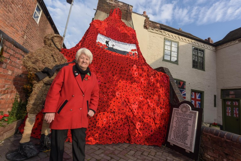 Pic by Michael Scott/Caters News - (PICTURED: Wendy Evans, 74 from New Invention in the West Midlands stands next to the poppy wall she helped to make which contains over 2,500 hand knitted poppies. The falling poppy wall is now on display at The Bell Inn, in Willenhall, West Midlands. Pic taken: 05/11/2018) - Thousands of knitted poppies have been hung from a historic pub in the run up to Remembrance Day in a stunt which took TWO YEARS to create. The huge wall of 2,500 flowers is now festooning the 400-year-old The Bell Inn in Willenhall, West Midlands, after local knitters painstaking created every individual poppy by hand over a 24-month period. SEE CATERS COPY