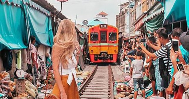 Travel blogger slammed for posing in front of a train