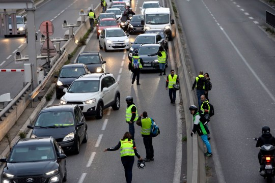 Demonstrators block a motorway exit in protest against fuel tax, in Marseille, southern France, Tuesday, Nov. 17, 2018. France is bracing for a nationwide traffic mess as drivers plan to block roads to protest rising fuel taxes, in a new challenge to embattled President Emmanuel Macron. (AP Photo/Claude Paris)