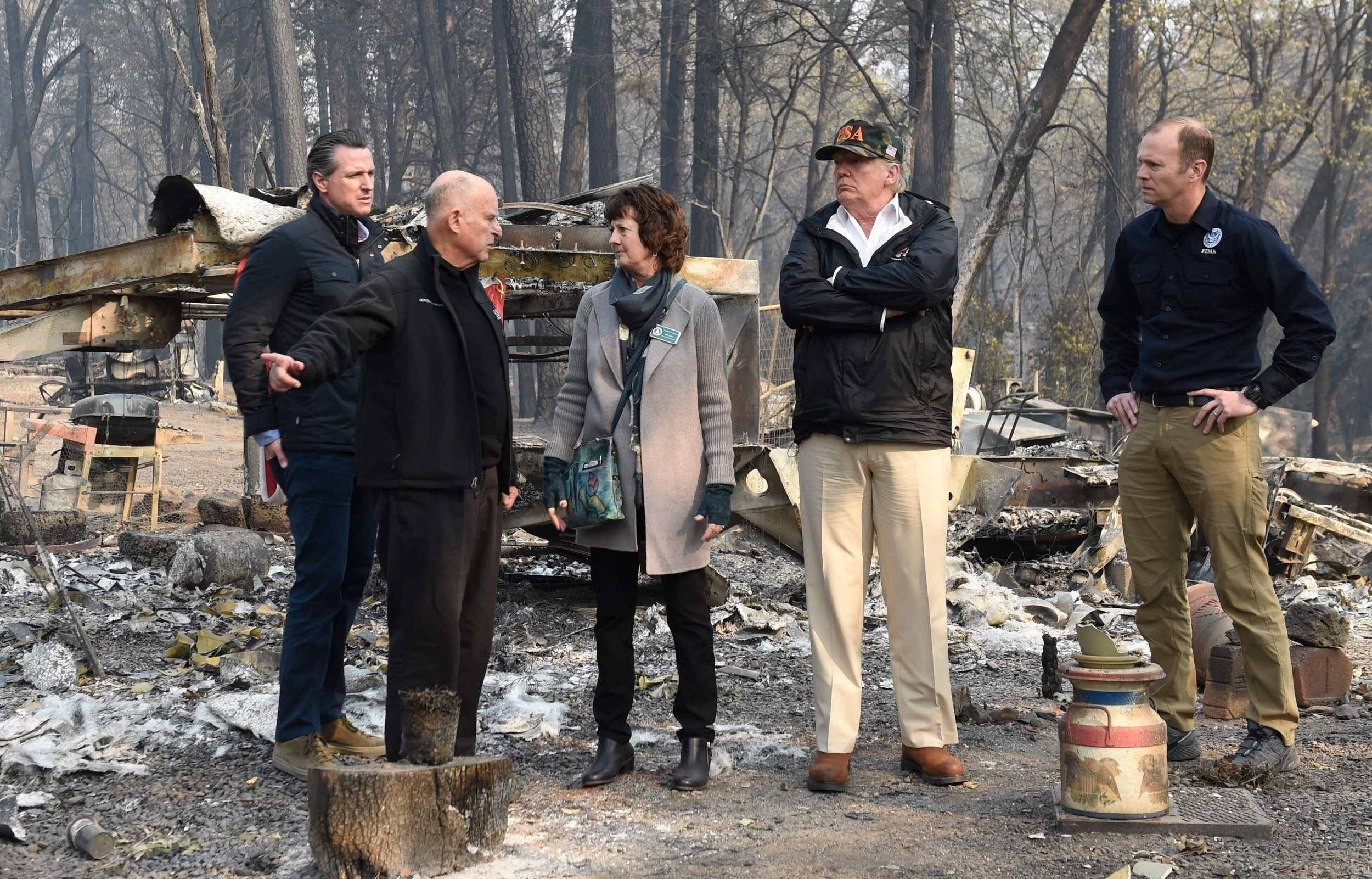 "US President Donald Trump (2R) looks on with Paradise Mayor Jody Jones (C), Governor of California Jerry Brown (L), Administrator of the Federal Emergency Management Agency, Brock Long (R), and Lieutenant Governor of California, Gavin Newson, as they view damage from wildfires in Paradise, California on November 17, 2018. - President Donald Trump arrived in California to meet with officials, victims and the ""unbelievably brave"" firefighters there, as more than 1,000 people remain listed as missing in the worst-ever wildfire to hit the US state. (Photo by SAUL LOEB / AFP)SAUL LOEB/AFP/Getty Images"