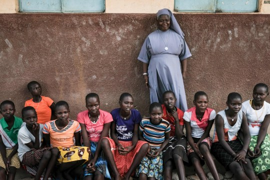 Magdalene Nantongo (C), head teacher of Kalas Girl's primary school, which hosts escaped girls from female genital mutilation (FGM) and child marriage, poses with students in Amudat town, northeast Uganda, on January 31, 2018. The UN estimates that over 200 million girls and women have experienced FGM which is a life-threatening procedure that involves the partial or total removal of a woman's external genitalia. February 6, 2018, marks the 6th International Day of Zero Tolerance for FGM. / AFP PHOTO / Yasuyoshi CHIBA (Photo credit should read YASUYOSHI CHIBA/AFP/Getty Images)