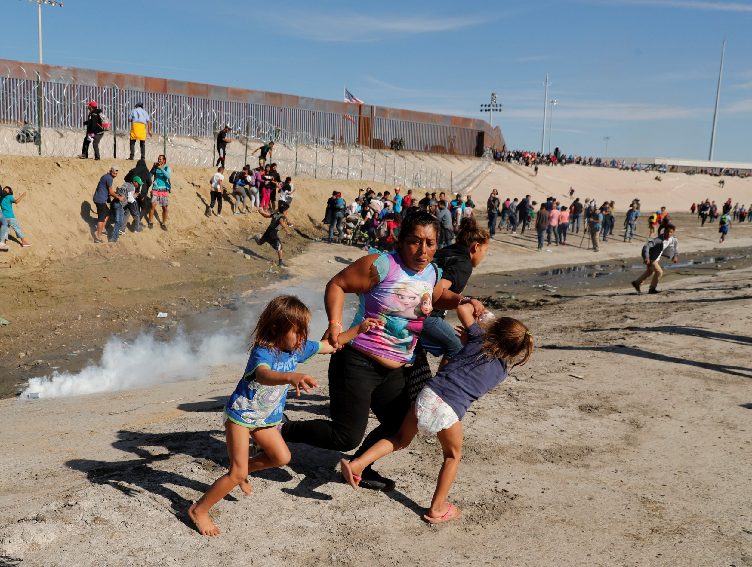 A migrant family, part of a caravan of thousands traveling from Central America en route to the United States, run away from tear gas in front of the border wall between the U.S and Mexico in Tijuana, Mexico November 25, 2018. REUTERS/Kim Kyung-Hoon