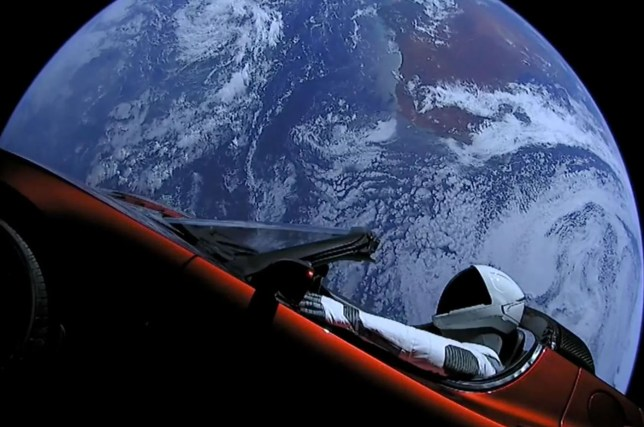 Starman behind the wheel of the Tesla Roadster with planet Earth in the background (Image: SpaceX)