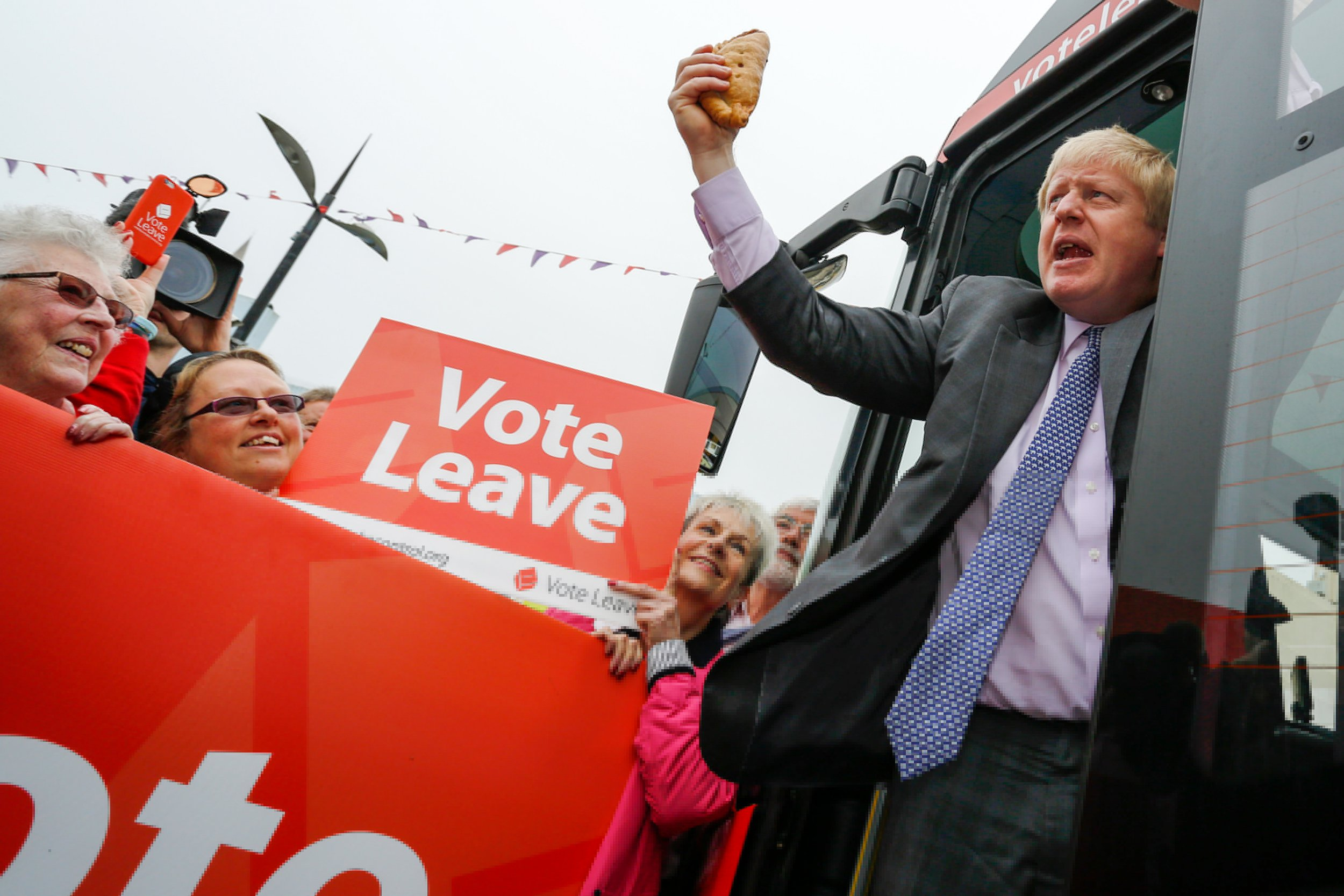 """Boris Johnson, the former mayor of London, waves a Cornish Pasty during the first day of a nationwide bus tour to campaign for a so-called Brexit in Truro, U.K., on Wednesday, May 11, 2016. While online polls suggest the contest for the June 23 referendum is too close to call, less frequent telephone polling has put the """"Remain"""" camp ahead. Photographer: Luke MacGregor/Bloomberg via Getty Images"""