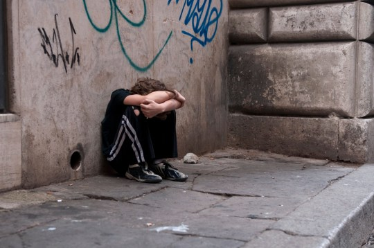 Young boy huddled and alone on a city street in Rome. Related: