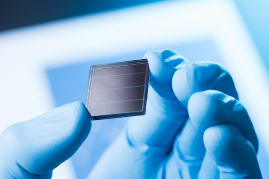 Scientist hold in hand small tile of new type efficient solar cell tile, solar technology research concept