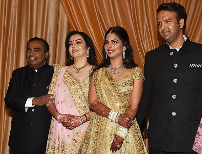 Indian businessman Mukesh Ambani (R) with wife Nita Ambani attends the wedding reception his daughter Isha Ambani (2nd R) who wedded Anand Piramal (R), son of Indian billionaire industrialist Ajay Piramal, in Mumbai on December 14, 2018. (Photo by Sujit Jaiswal / AFP)SUJIT JAISWAL/AFP/Getty Images