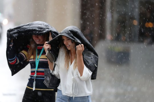 Pedestrians dash through the streets of central London during a downpour on August 10, 2018. (Photo by Daniel LEAL-OLIVAS / AFP) (Photo credit should read DANIEL LEAL-OLIVAS/AFP/Getty Images)