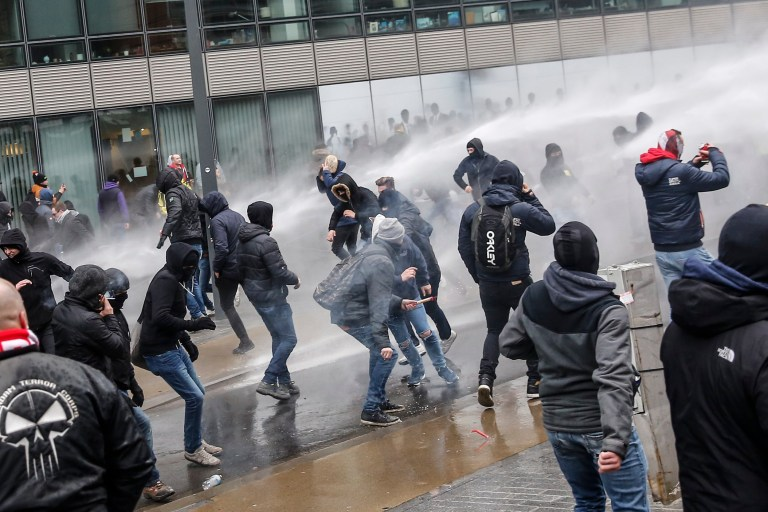 epa07235357 Protesters of right-wing and far-right Flemish associations are shot with police water cannons during the 'March Against Marrakech' demonstration near European institutions headquarters in Brussels, Belgium, 16 December 2018. Anti-immigration protesters took to the streets of Brussels to denounce the Global Compact on Migration adopted in Marrakesh and approved by the Belgian Prime Minister. The march was organized by several right-wing and far-right Flemish associations such as KVHV, NSV, Schild & Vrienden, Voorpost and Vlaams Belang Jongeren. EPA/JULIEN WARNAND