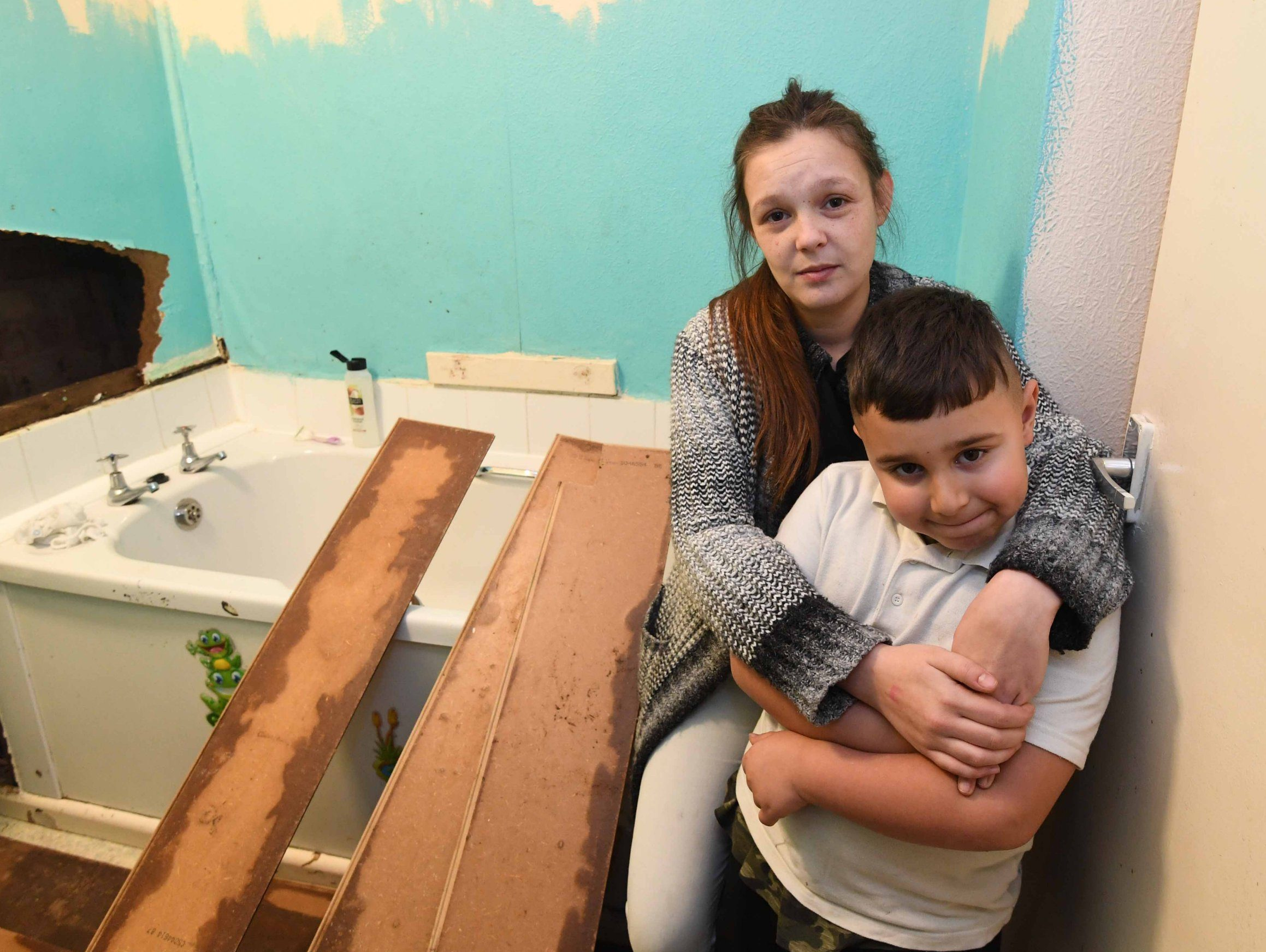 Pictured Charlene Lewis with son Kameron aged 7 is having problems with the raw sewage waste from the flat above her running into the bathroom sink and bath at the set flats in Hurst Lane, Castle Bromwich.