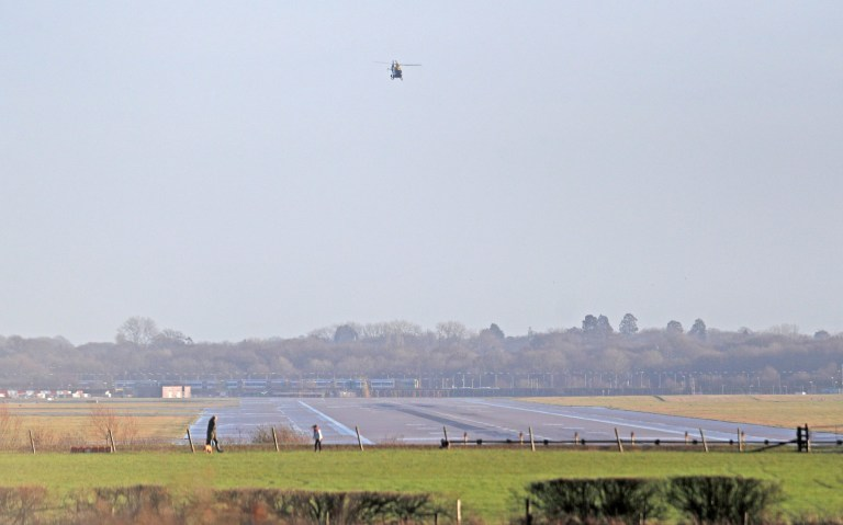 A police helicopter flies over the closed runway at Gatwick Airport after drones flying illegally over the airfield forced the closure of the airport, in Gatwick, Britain, December 20, 2018. REUTERS/Peter Nicholls