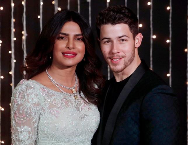 Bollywood actress Priyanka Chopra and musician Nick Jonas stand for photographs at their wedding reception in Mumbai, India, Thursday, Dec 20, 2018. (AP Photo/Rajanish Kakade)