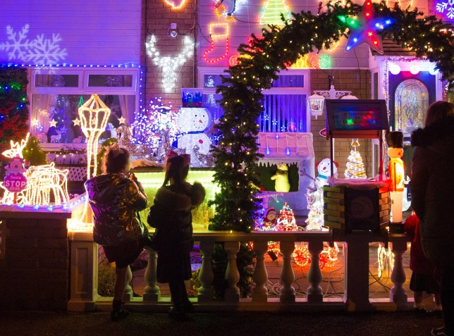 MERCURY PRESS. Wirral, UK. Pictured: Children enjoying the christmas lights festooning the house in Saughall Massie, Wirral. A Christmas crazy couple have spent five weeks covering their house in festive decorations for the TWENTIETH year running. Karen, 55, and Frank Williams, 56, have been decorating the front of their house, on Amberley Close, Wirral, for the past 20 years to give their neighbours festive cheer. Despite initially covering their house in lights for the first eight years just for their own enjoyment, the couple have since been raising money for charity Claire House Childrens Hospice and have collected over ?20,000. SEE MERCURY COPY