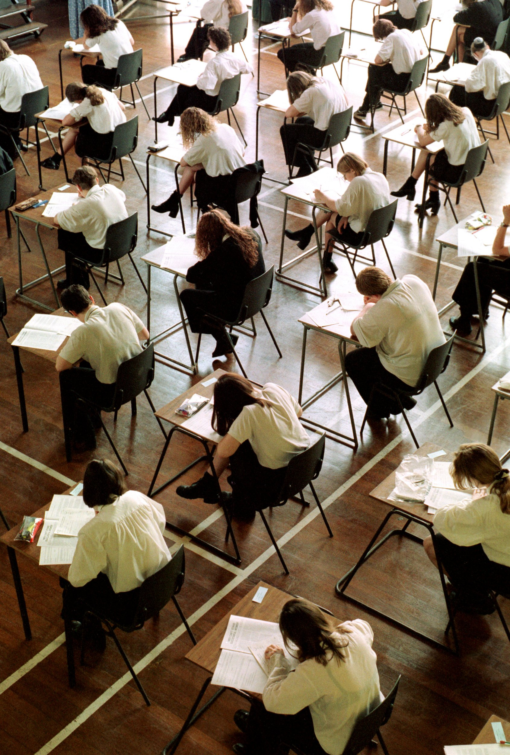 School students from year 11 at Northgate High School sit and take there GCSE English exams while working at temporary desks in the main hall of the school in Dereham, Norfolk, U.K., in June, 1996. (Photo by Bryn Colton/Getty Images)
