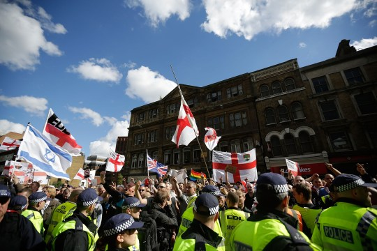 """LONDON, ENGLAND - SEPTEMBER 07: Members of the English Defence League, rally for speeches by the far-right organisation's leader and deputy leader at Aldgate on September 7, 2013 in London, England. The EDL far-right organisation have had restrictions placed on the march by the Metropolitan police due to the fear of """"serious public disorder"""", but it will still proceed to the edge of Tower Hamlets, which is home to a large population of ethnic minorities. (Photo by Matthew Lloyd/Getty Images)"""