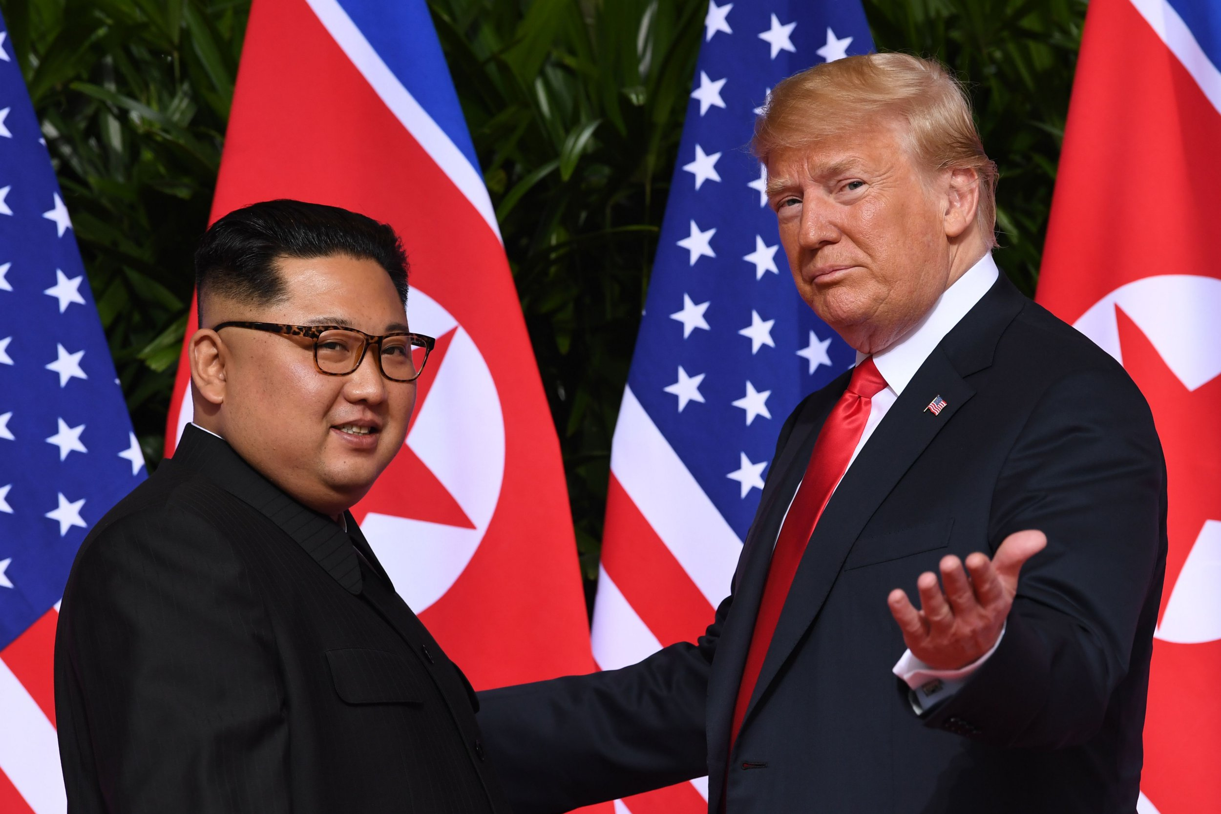 """(FILES) In this file photo taken on June 11, 2018 US President Donald Trump (R) gestures as he meets with North Korea's leader Kim Jong Un (L) at the start of their historic US-North Korea summit, at the Capella Hotel on Sentosa island in Singapore. - US President Donald Trump said on December 1, 2018, he hoped to organize a second summit with North Korean leader Kim Jong Un in early 2019, perhaps as soon as January or February. Trump told reporters traveling home to Washington with him aboard Air Force One from Argentina that """"three sites"""" were in consideration for the meeting, a follow-up to their historic summit in Singapore in June. (Photo by SAUL LOEB / AFP)SAUL LOEB/AFP/Getty Images"""