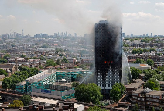 TOPSHOT - Smoke and flames billows from Grenfell Tower as firefighters attempt to control a blaze at a residential block of flats on June 14, 2017 in west London. At least six people were killed Wednesday when a massive fire tore through a London apartment block in the middle of the night, with witnesses reporting terrified people had leapt from the 24-storey tower. / AFP PHOTO / Adrian DENNIS (Photo credit should read ADRIAN DENNIS/AFP/Getty Images)