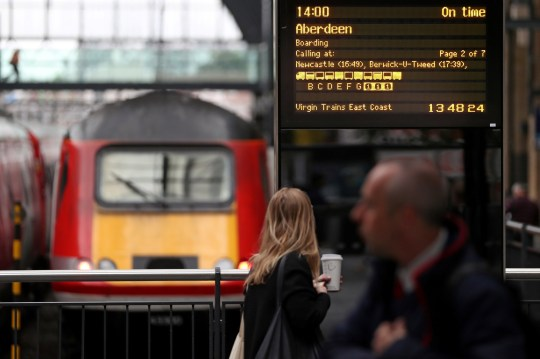 A passenger passes an electronic display board for a Virgin Trains East Coast main line train service to Aberdeen, as he walks along the concourse at London Kings Cross rail station in London on May 16, 2018. - The British government announced on Wednesday that it would resume control of the East Coast Main Line rail service, privatised three years ago, following the termination of the franchise agreement with Virgin Trains East Coast (VTEC) - a joint venture between Stagecoach and Virgin. Trains will continue to run by the Department for Transport (DfT) through an operator of last resort (OLR). (Photo by Daniel LEAL-OLIVAS / AFP) (Photo credit should read DANIEL LEAL-OLIVAS/AFP/Getty Images)