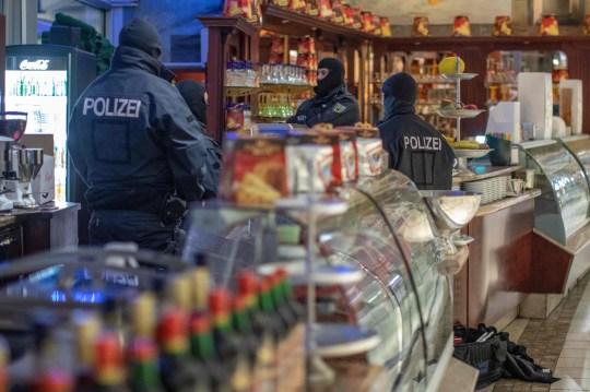 """Policemen raid an ice cafe in Duisburg, western Germany, on December 5, 2018. - Around 90 people suspected of belonging to the notorious 'Ndrangheta mafia were rounded up in raids across several European and Latin American countries, Italian police said. The suspects are thought to be key members of the powerful organised crime syndicate based in southern Italy. They are accused of committing """"serious crimes"""" including activities linked to international drug trafficking. The vast anti-mafia operation was carried out by Italy's anti-mafia and anti-terrorism force in collaboration with German, Belgian and Dutch authorities. (Photo by Christoph Reichwein / dpa / AFP) / Germany OUTCHRISTOPH REICHWEIN/AFP/Getty Images"""