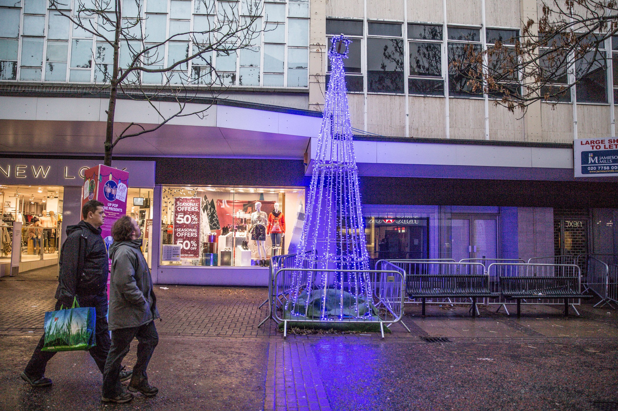 MERCURY PRESS. Birkenhead, UK. 6/12/18. Pictured: Shoppers pass the Christmas tree installed in Birkenhead, Wirral. A towns holiday cheer has turned to festive fury over their waste of space Christmas tree that many say looks like a bit of scaffolding. Residents of Birkenhead on the Wirral, Merseyside, have been left stunned by this years truly appalling Christmas installation. The tree - a hollow cone-shaped metal frame adorned with LED lights and a Christmas present on top - was installed by the Wirral Chamber of Commerce. SEE MERCURY COPY
