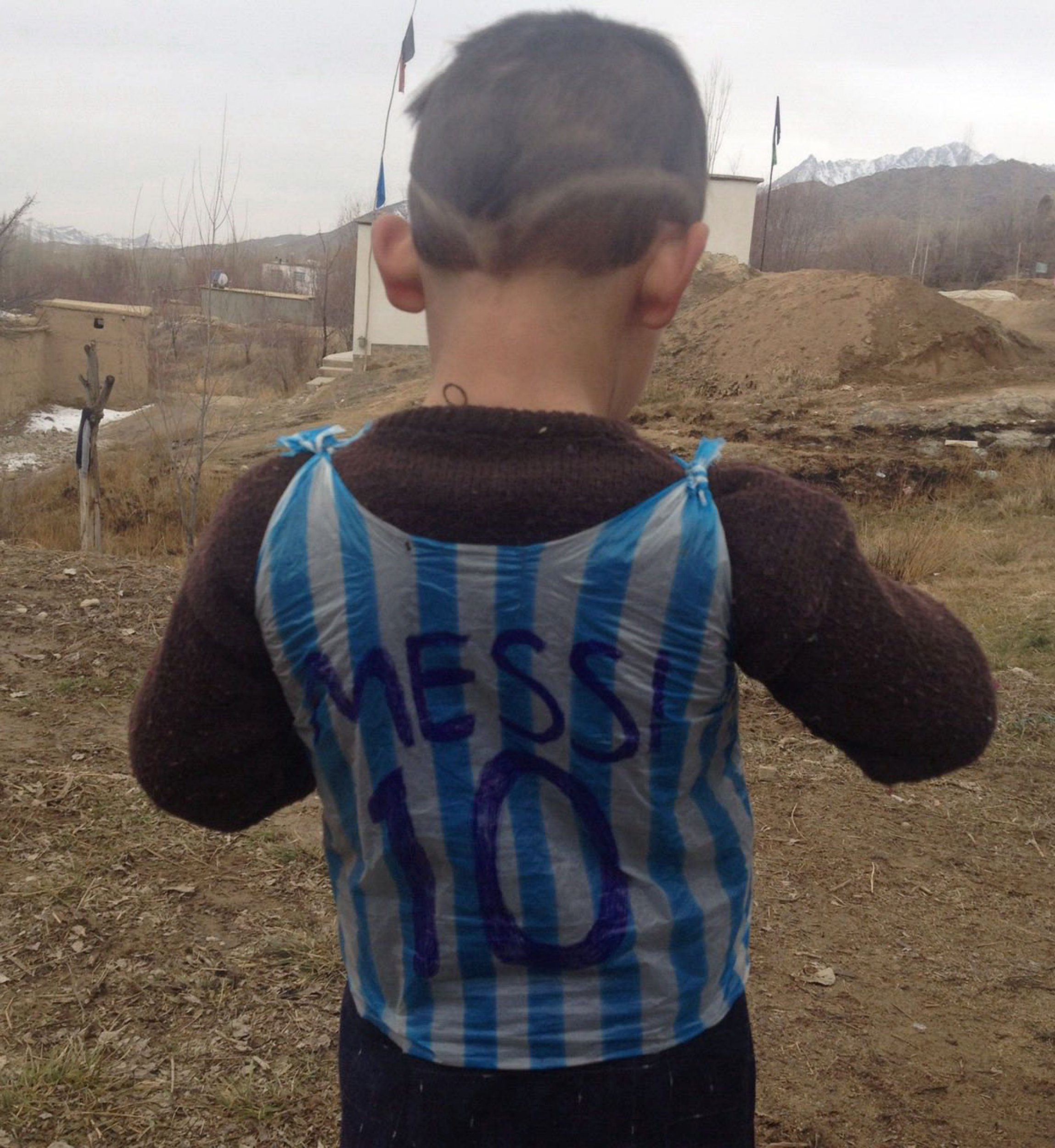 This photograph taken on January 24, 2016 and provided by the family of Afghan boy and Lionel Messi fan Murtaza Ahmadi, 5, shows him wearing a plastic bag jersey in Jaghori district of Ghazni province. A five-year-old Afghan boy has become an internet star after pictures went viral of him wearing an Argentina football shirt made out of a plastic bag, complete with his hero Lionel Messi's name. AFP PHOTO / AFP / STR (Photo credit should read STR/AFP/Getty Images)