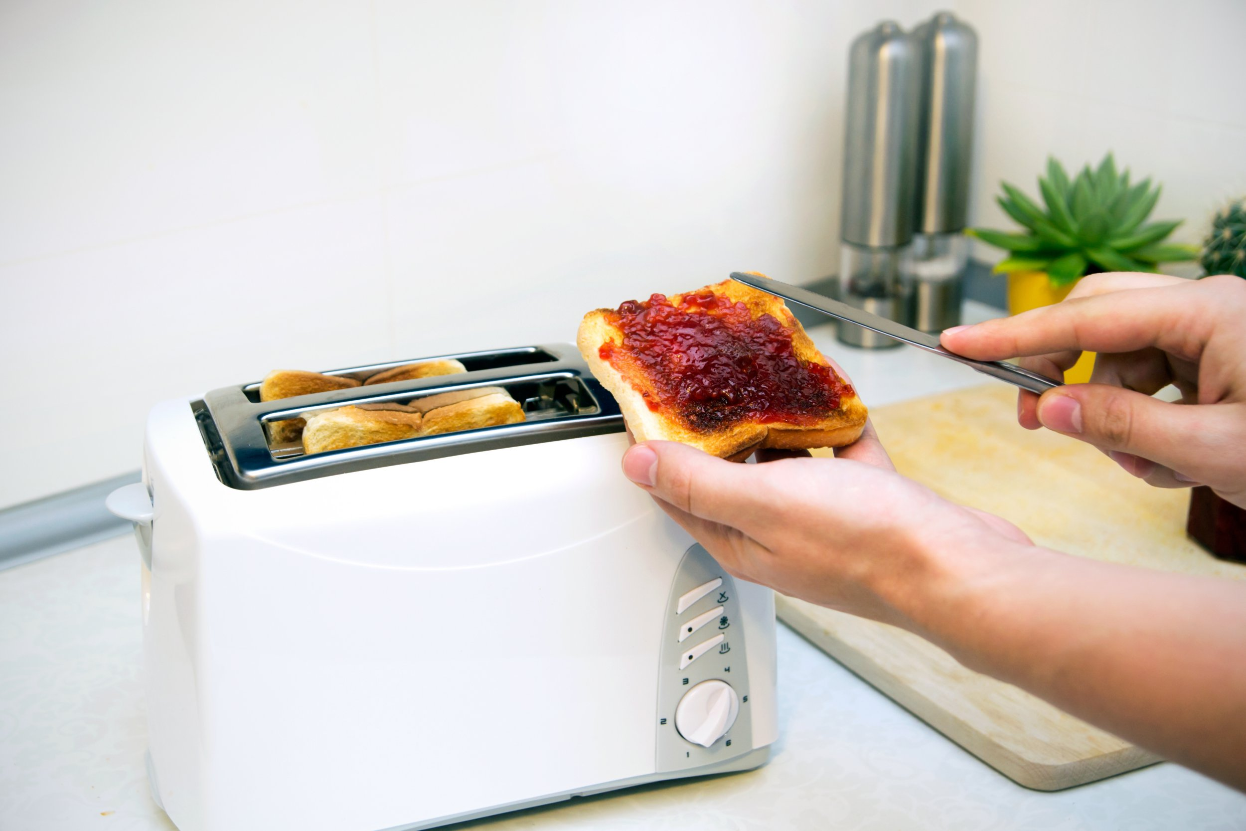 Preparing toast with jam for breakfast