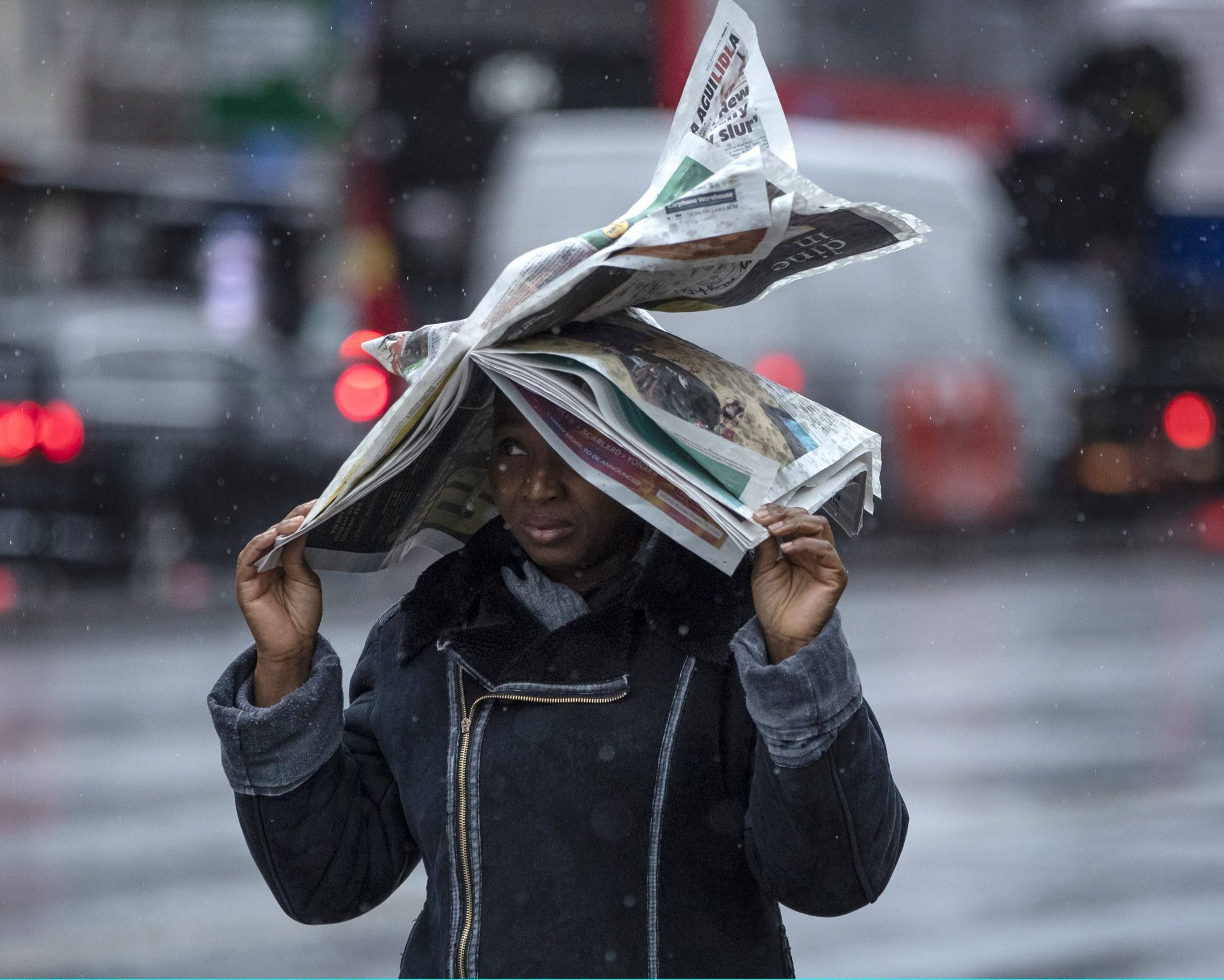 LONDON, ENGLAND - DECEMBER 07: A woman uses a newspaper to shield herself from the rain at Elephant and Castle on December 7, 2018 in London, England. The Met Office has issued a yellow weather warning for the South West of England and Wales with torrential rain and strong winds expected across much of the country over the weekend. (Photo by Dan Kitwood/Getty Images)