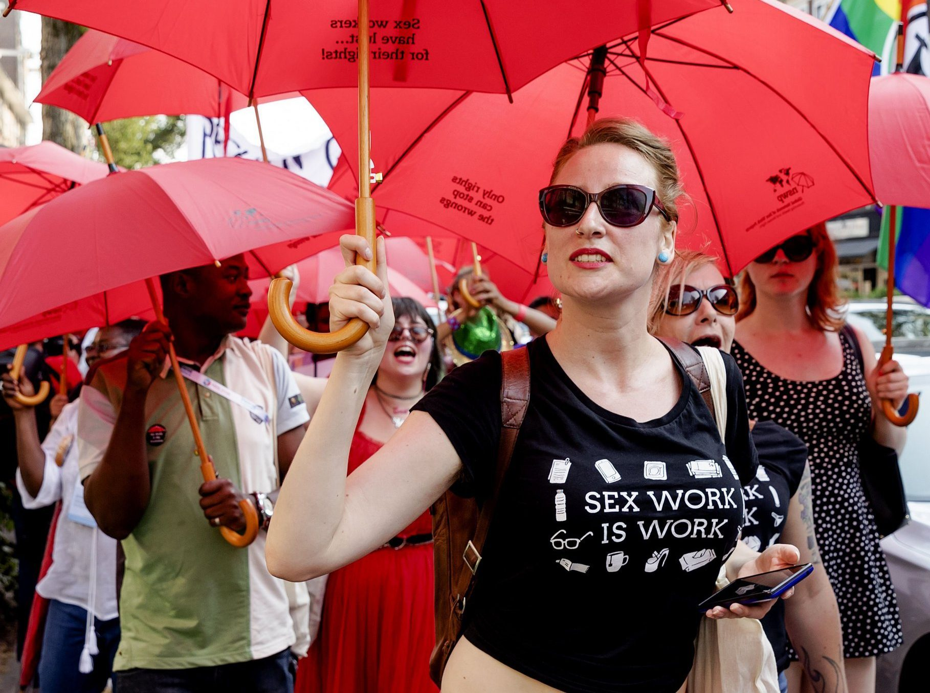 "Sex workers from more than 36 countries demonstrate against legislation around the world that endangers their lives, as a side event of the AIDS2018 conference in Amsterdam on July 24, 2018. - The crowd started the walk at the RAI (where the AIDS2018 conference takes place) and ended in the red light district ""De Wallen"" in the center of Amsterdam. (Photo by Robin van Lonkhuijsen / ANP / AFP) / Netherlands OUT (Photo credit should read ROBIN VAN LONKHUIJSEN/AFP/Getty Images)"