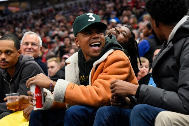 Chance the Rapper laughs while sitting near the court during the second half of an NBA basketball game between the Chicago Bulls and the Minnesota Timberwolves Wednesday, Dec. 26, 2018, in Chicago. (AP Photo/Matt Marton)