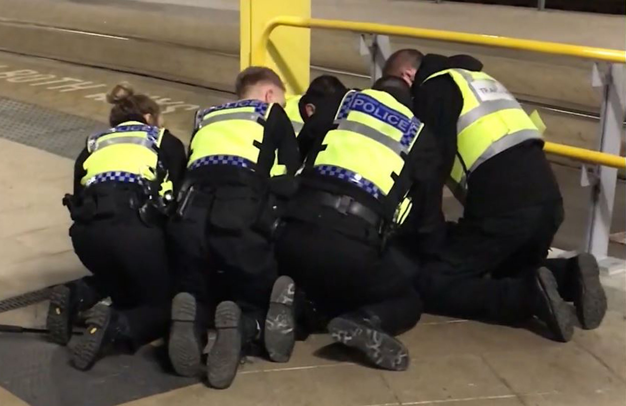 Handout photo issued by Sam Clack of police restraining a man after he stabbed three people at Victoria Station in Manchester last night. PRESS ASSOCIATION Photo. Issue date: Tuesday January 1, 2019. Two commuters - a man and woman in their 50s - were taken to hospital with knife injuries and a British Transport Police (BTP) officer was stabbed in the shoulder. Police said a man was arrested on suspicion of attempted murder and remains in custody. See PA story POLICE Manchester. Photo credit should read: Sam Clack/PA Wire NOTE TO EDITORS: This handout photo may only be used in for editorial reporting purposes for the contemporaneous illustration of events, things or the people in the image or facts mentioned in the caption. Reuse of the picture may require further permission from the copyright holder.