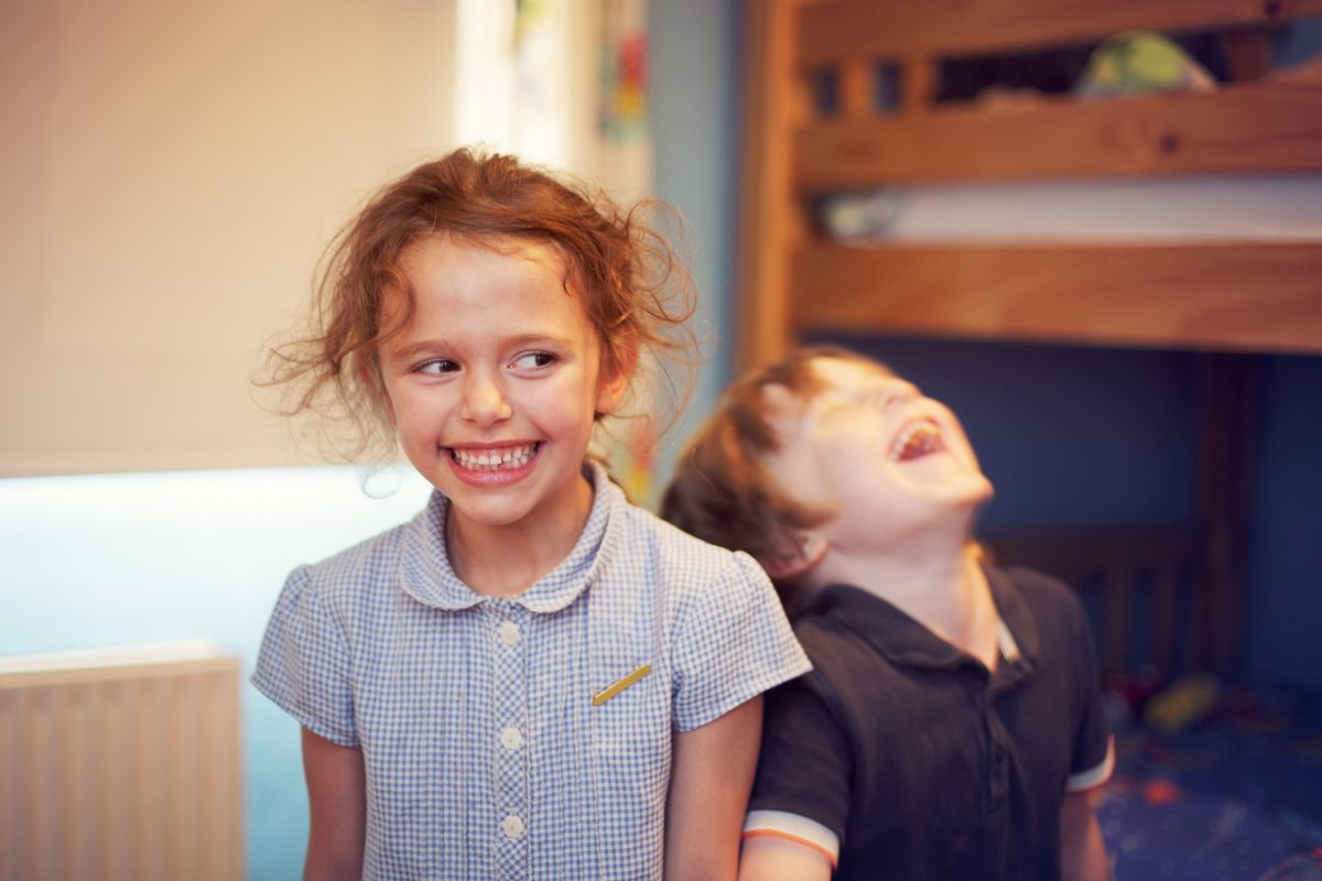Two children laughing and smiling in a bedroom with a bunkbed