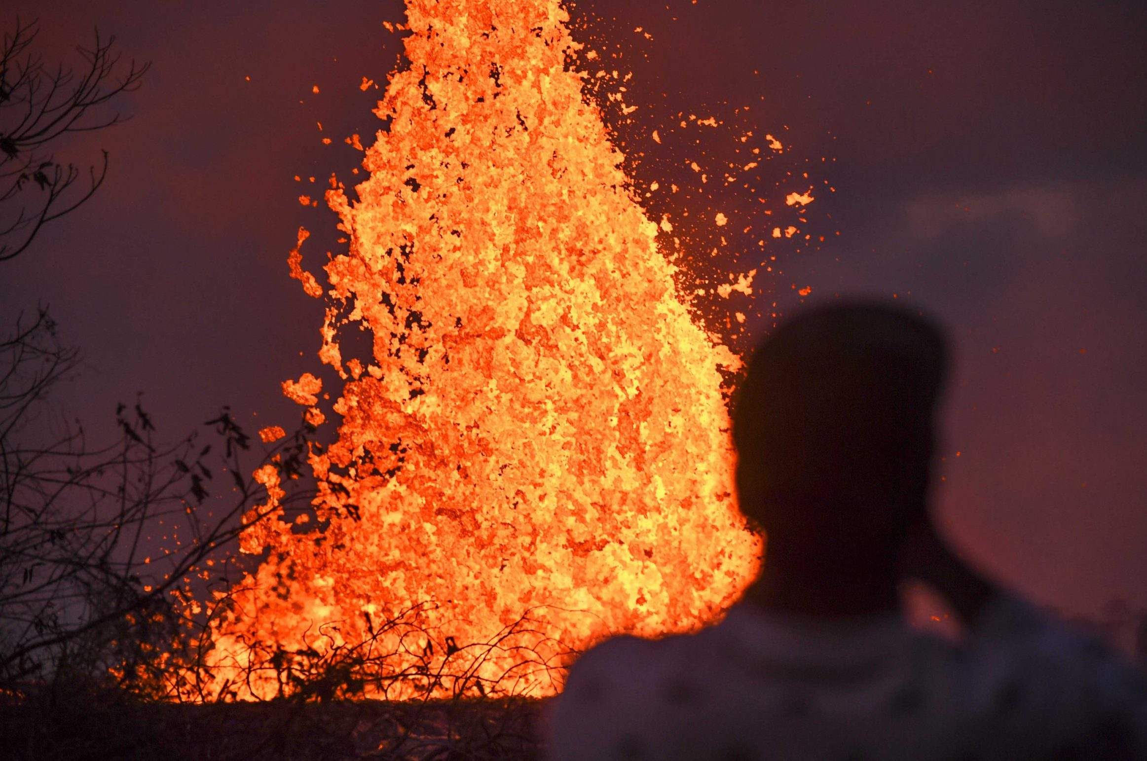 Mandatory Credit: Photo by Robert Hanashiro-USA Today Sport/Sipa USA/REX/Shutterstock (9692422e) A resident watches lava from Kilauea Volcano shoot into the air out of cracks in the earth Kilauea volcano eruption, Pahoa, Hawaii - 23 May 2018