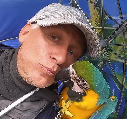 "Pic Shows: Parrot owner Joseph Verdyck; A hunter has admitted blasting a rare parrot out of the sky while it was being exercised by its owner because it was not illegal to shoot exotic birds. Parrot owner Joseph Verdyck from the Belgian town of Westmalle not only saw his pet shot, but then watched in vain as it was partially eaten by hunting dogs. He had taken his pet parrots Rambo and Mera for a fly in the outdoors. He had raised them by himself after hatching them from eggs, and even taught them to fly. He got the permission of a farmer to let the ara macaws, worth several thousand pounds each, fly over one of his fields. Verdyck said: ""Rambo became a fully fledged free flight bird after three years. According to experts he was one of the best trained parrots in Belgium. ""He is often allowed together with Mero to fly free for the day, in the summer a bit longer than in winter."" Verdyck was however unaware that hunters were in the area, and within minutes one of them took aim at Rambo and blasted him from the sky. He then saw to his horror how the hunting dogs owned by the men immediately ran towards the parrot and savaged the poor bird in front of his eyes. An image shows the remains of the dead parrot on the ground with its red harness clearly visible. A shocked Verdyck immediately confronted the hunter who shot his beloved pet animal. Verdyck said: ""He apologised because he did not know it was my bird and said that he would have never done it if he had realised the owner was nearby, and that it was not an escaped animal."" The hunter said that he saw the bird flying over in the sky and decided to shoot it as hunting exotic bird species is allowed in Belgium. He promised Verdyck he would contact his insurance company to see if the pet owner can be reimbursed. Verdyck however filed a criminal complaint against the hunter. He said: ""The man just shot for fun at Rambo. A hunter hunts for game: rabbits, pigeons and pheasant. Not a brightly-coloured parro"