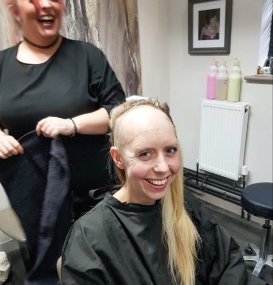 Pic from Caters News - (Pictured: Katie Smith, 33, from Stourbridge, West Mids in the Optima Hair studio getting her new hair stuck on with glue.) - A brave mum who was left half bald after brain tumour treatment has showcased her luscious locks thanks to a pioneering GLUE. Katie Smith, 33, from Stourbridge, West Mids, was left permanently bald on the front part of her head after undergoing gruelling cancer treatment in a bid to save her life. After initially being diagnosed with a grade 2 brain tumour in 2015, Katie was told the devastating news that the cancerous mass had returned last March. SEE CATERS COPY