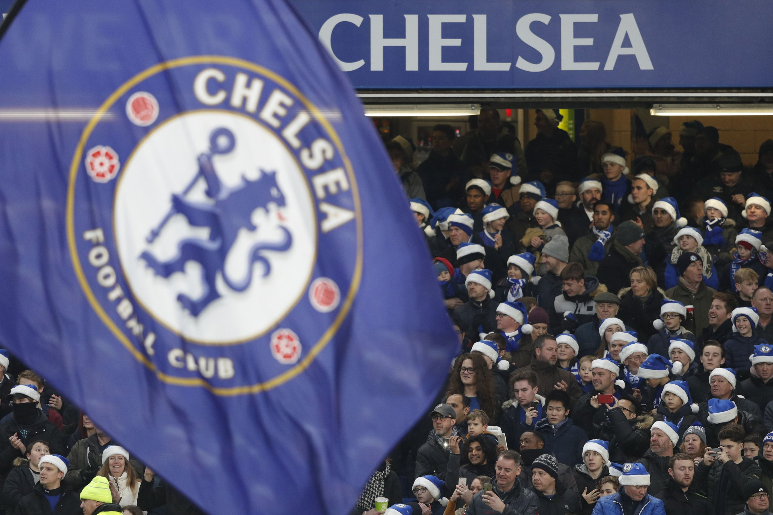 Chelsea fans wear blue santa hats during the English Premier League football match between Chelsea and Southampton at Stamford Bridge in London on December 16, 2017. (Photo by Adrian DENNIS / AFP) / RESTRICTED TO EDITORIAL USE. No use with unauthorized audio, video, data, fixture lists, club/league logos or 'live' services. Online in-match use limited to 75 images, no video emulation. No use in betting, games or single club/league/player publications. / (Photo credit should read ADRIAN DENNIS/AFP/Getty Images)
