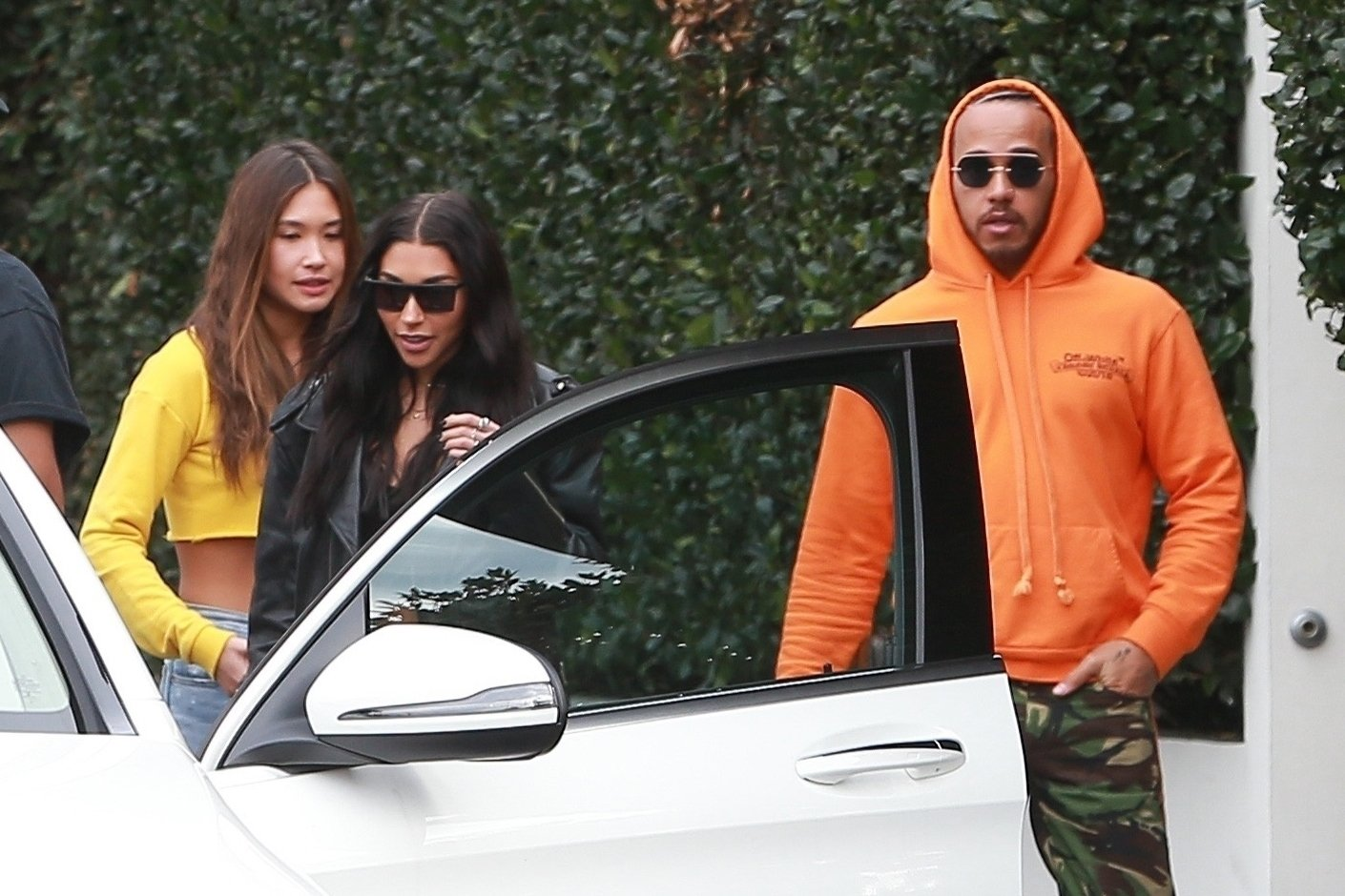 Lewis Hamilton is far from 'slumming' it as he leaves fancy restaurant with bunch of models