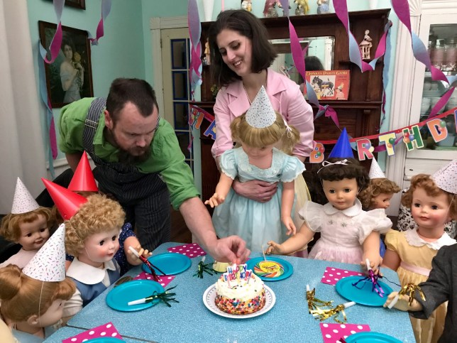 CROSS HILL, SOUTH CAROLINA, USA: Birthday party for the dolls. THIS VINTAGE loving couple created an Instagram account dedicated to their LIFE-SIZE PLASTIC DOLL CHILDREN after their friends were posting pictures of their real families on Facebook to address those constantly asking when they were going to start a family of their own. Childhood sweethearts, applications scientist, Madeline Dressel (34) and her communications technician husband, Malachi (35) from Cross Hill, South Carolina, USA, grew up together and have been married for four years. The pair have a passion for all things vintage and spend their spare time scouring charity shops, garage sales and flea markets to add to their collection of dolls, vintage kitchenware, mid-century furniture, toys, tools and d??cor which they then spend time upcycling and make use of these items in their home. The pair have many vintage appliances which include radios, toaster, vacuum cleaner, gas stove and fridge in their home that are over 60-years old and still in peak condition. Madeline has collected dolls ever since she was a child and has a passion for vintage Barbies of which she has a collection of 75 but has collected toddler sized dolls from the 1950s and 60s since 2016. Madeline and Malachi can spend anywhere between a few hours to a few days restoring the dolls they find through hunting thrift shops and markets. Madeline and Malachi set up their Instagram, all.my.plastic.children last year as a parody account documenting their plastic family life after they noticed their Facebook feeds were saturated with their friends posting pictures with their real children. Since then, they have been staging their ???family??? portraits and have celebrated Christmas and birthdays all with a retro twist. MDWfeatures / Madeline Dressel
