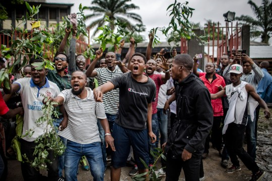 Protesters waiting to cast their ballot, demonstrate outside the College St Raphael polling station, in Kinshasa, on December 30, 2018 while DRC's electoral commission president arrives for the DR Congo's general elections. - Voters in the Democratic Republic of Congo went to the polls on December 30, 2018 in elections that will shape the future of their vast, troubled country, amid fears that violence could overshadow the ballot. (Photo by Luis TATO / AFP) (Photo credit should read LUIS TATO/AFP/Getty Images)