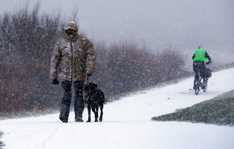 A man walks his dog through the snow in Whitley Bay, North Tyneside. PRESS ASSOCIATION Photo. Picture date: Thursday January 17, 2019. Temperatures dipped below freezing across Scotland and the far north of England overnight, with a low of minus 3.4 (26F) recorded at Great Dun Fell in Cumbria. See PA story WEATHER Cold. Photo credit should read: Owen Humphreys/PA Wire